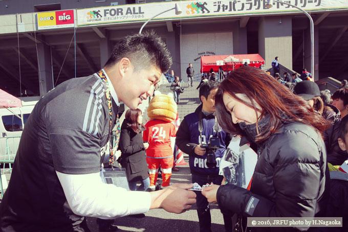グリーティングタイムで、選手からステッカーを受け取る女性