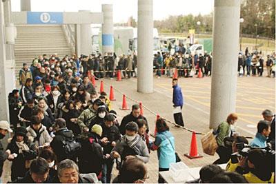 開門する前に列に並ぶ観客
